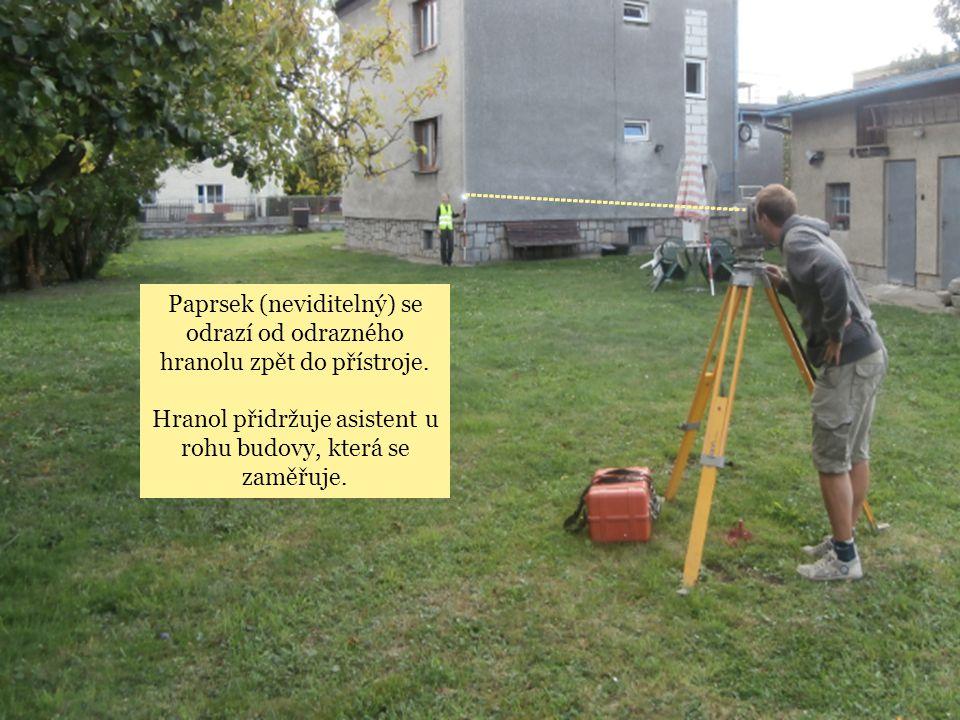 Hranol přidržuje asistent u rohu budovy, která se zaměřuje.