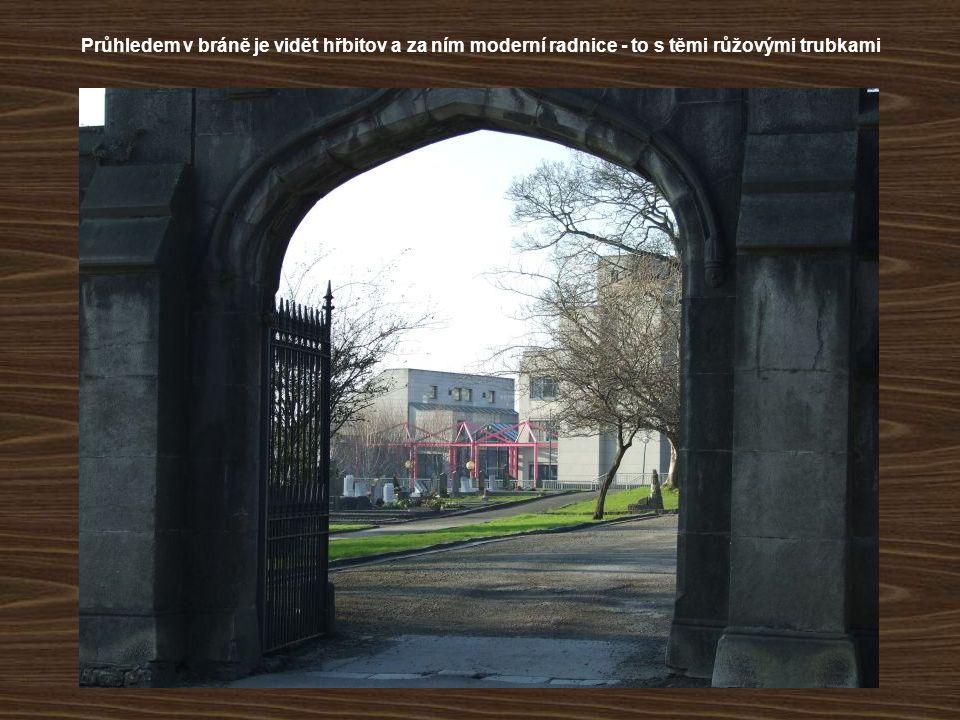 Průhledem v bráně je vidět hřbitov a za ním moderní radnice - to s těmi růžovými trubkami