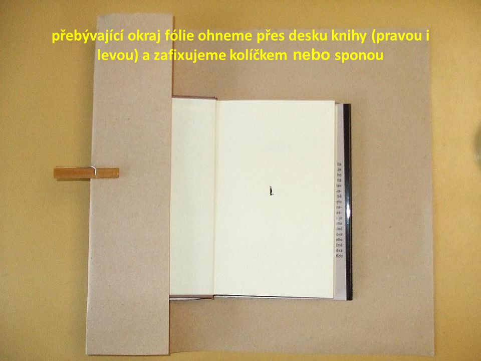 přebývající okraj fólie ohneme přes desku knihy (pravou i levou) a zafixujeme kolíčkem nebo sponou