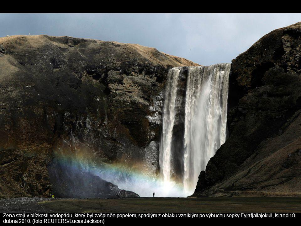 Žena stojí v blízkosti vodopádu, který byl zašpiněn popelem, spadlým z oblaku vzniklým po výbuchu sopky Eyjafjallajokull, Island 18.