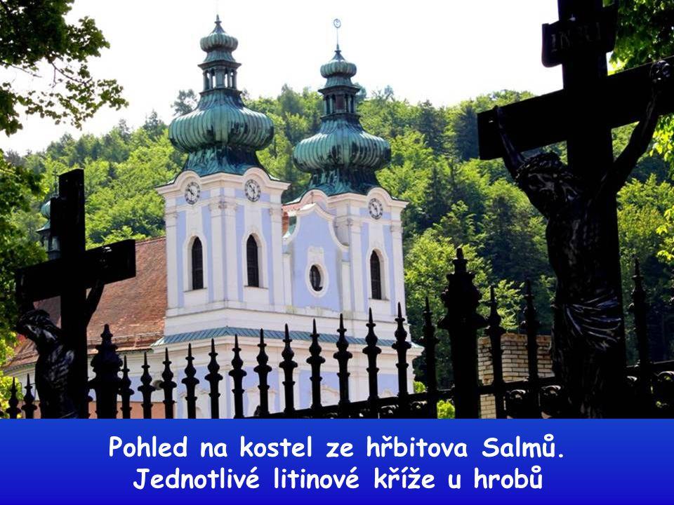 Pohled na kostel ze hřbitova Salmů. Jednotlivé litinové kříže u hrobů