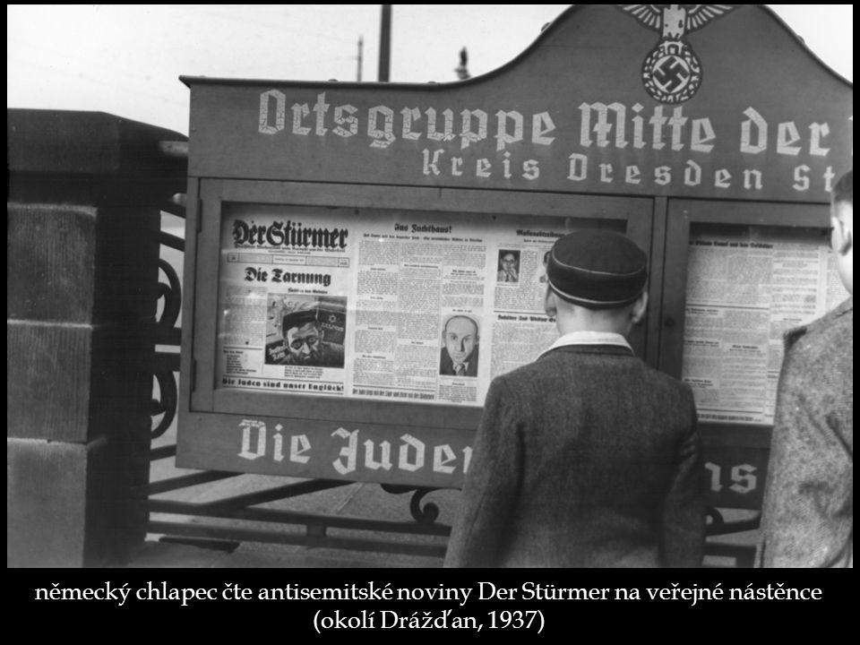 německý chlapec čte antisemitské noviny Der Stürmer na veřejné nástěnce (okolí Drážďan, 1937)
