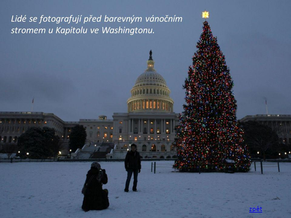 Lidé se fotografují před barevným vánočním stromem u Kapitolu ve Washingtonu.