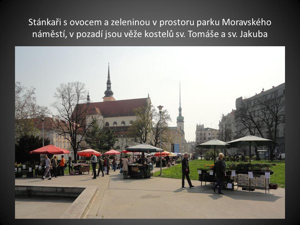 Stánkaři s ovocem a zeleninou v prostoru parku Moravského náměstí, v pozadí jsou věže kostelů sv.
