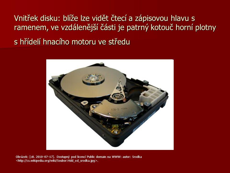 Vnitřek disku: blíže lze vidět čtecí a zápisovou hlavu s ramenem, ve vzdálenější části je patrný kotouč horní plotny s hřídelí hnacího motoru ve středu