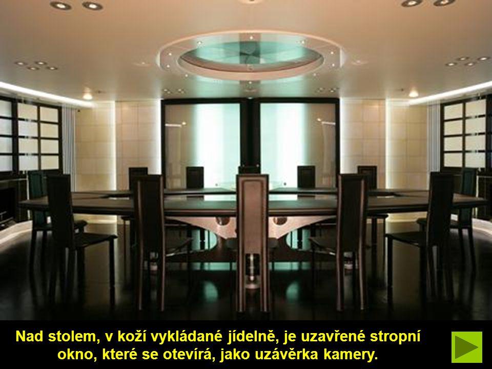Nad stolem, v koží vykládané jídelně, je uzavřené stropní okno, které se otevírá, jako uzávěrka kamery.