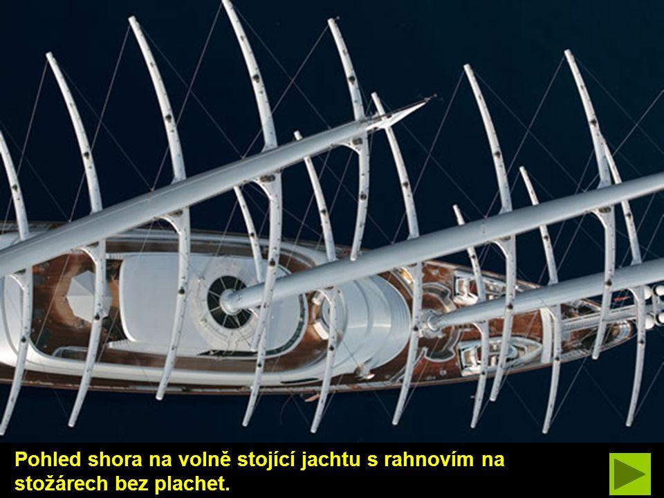 Pohled shora na volně stojící jachtu s rahnovím na stožárech bez plachet.