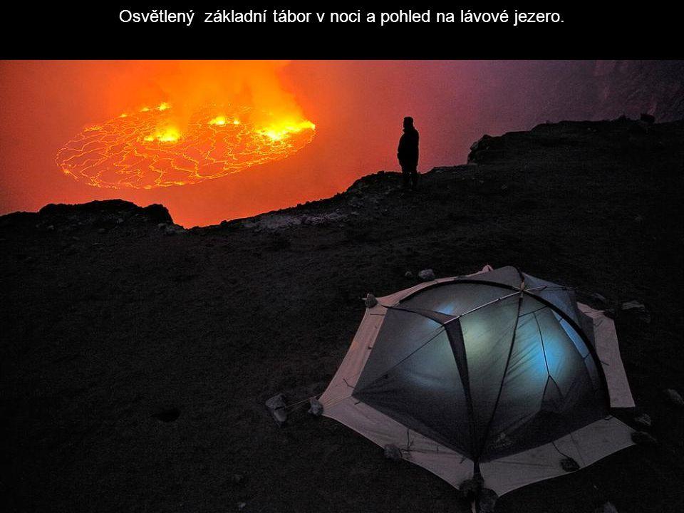Osvětlený základní tábor v noci a pohled na lávové jezero.