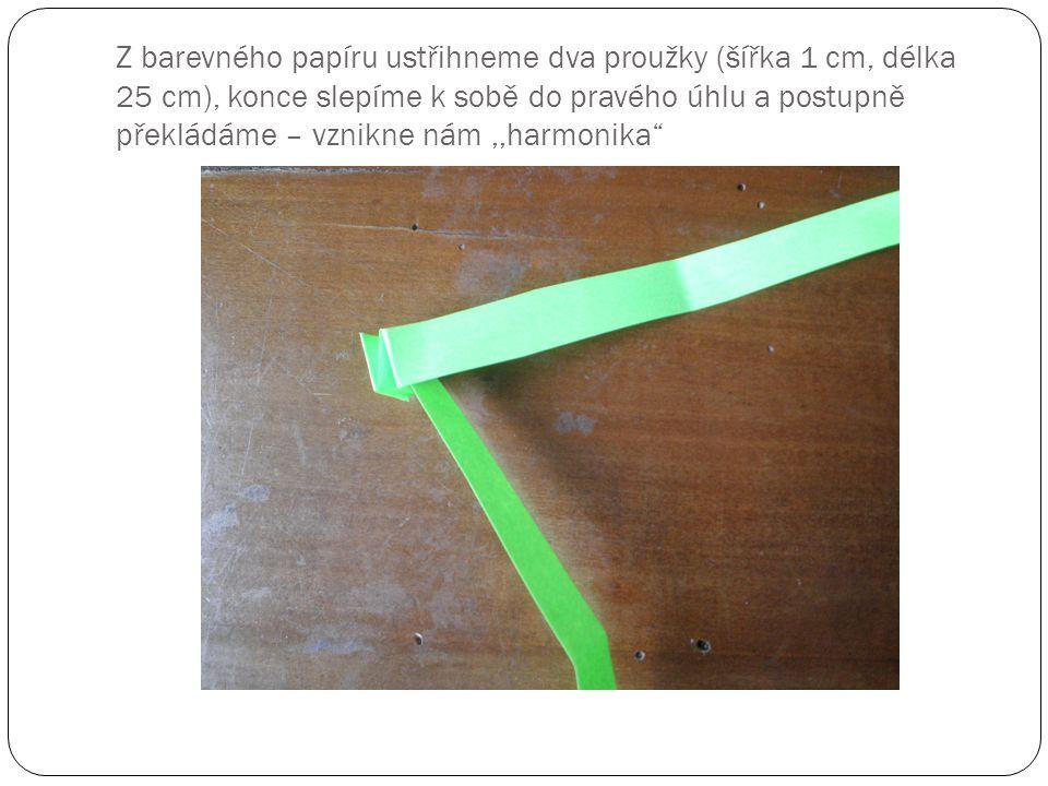 Z barevného papíru ustřihneme dva proužky (šířka 1 cm, délka 25 cm), konce slepíme k sobě do pravého úhlu a postupně překládáme – vznikne nám ,,harmonika