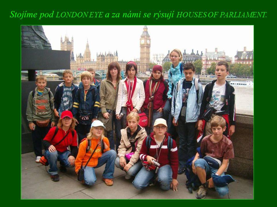 Stojíme pod LONDON EYE a za námi se rýsují HOUSES OF PARLIAMENT.