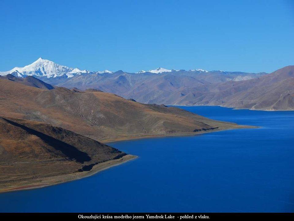 Okouzlující krása modrého jezera Yamdrok Lake - pohled z vlaku.