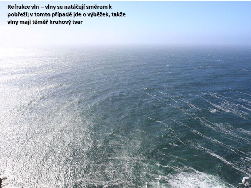 Refrakce vln – vlny se natáčejí směrem k pobřeží; v tomto případě jde o výběžek, takže vlny mají téměř kruhový tvar