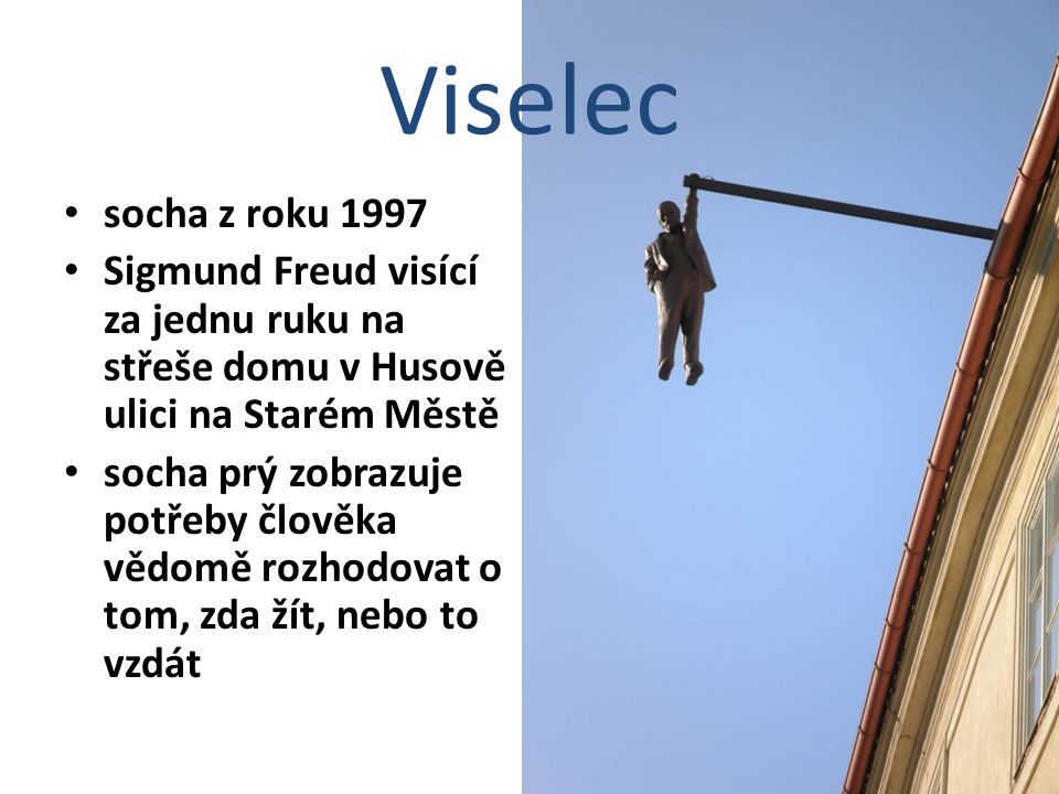 Viselec socha z roku 1997. Sigmund Freud visící za jednu ruku na střeše domu v Husově ulici na Starém Městě.