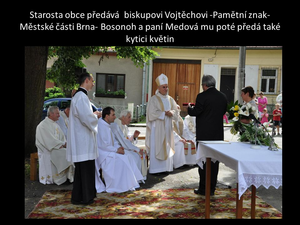 Starosta obce předává biskupovi Vojtěchovi -Pamětní znak- Městské části Brna- Bosonoh a paní Medová mu poté předá také kytici květin
