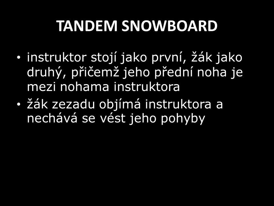 TANDEM SNOWBOARD instruktor stojí jako první, žák jako druhý, přičemž jeho přední noha je mezi nohama instruktora.