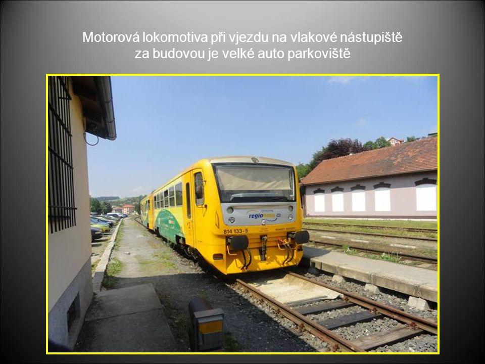 Motorová lokomotiva při vjezdu na vlakové nástupiště za budovou je velké auto parkoviště