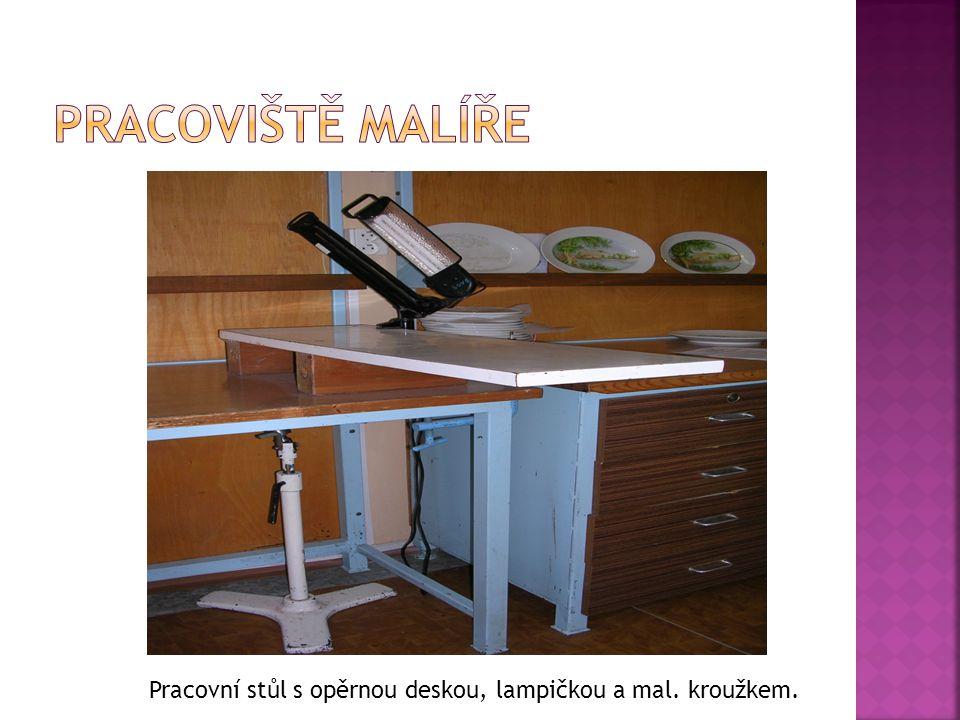 Pracoviště malíře Pracovní stůl s opěrnou deskou, lampičkou a mal. kroužkem.