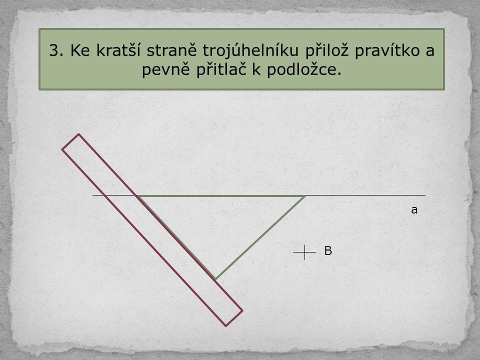 3. Ke kratší straně trojúhelníku přilož pravítko a pevně přitlač k podložce.
