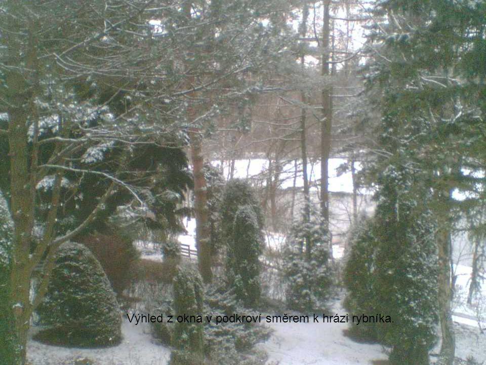 Výhled z okna v podkroví směrem k hrázi rybníka.