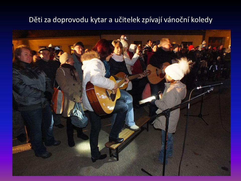 Děti za doprovodu kytar a učitelek zpívají vánoční koledy