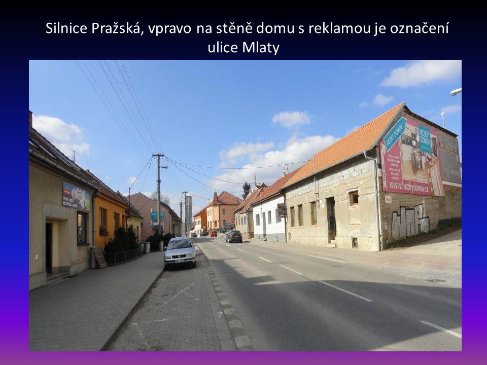 Silnice Pražská, vpravo na stěně domu s reklamou je označení ulice Mlaty